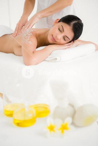 Woman enjoying a salt scrub massage