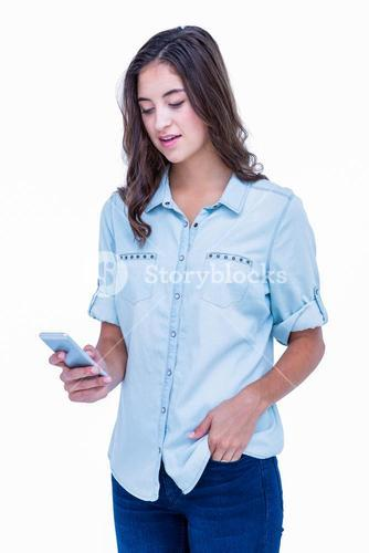 Pretty hipster with hand in pocket using her smartphone