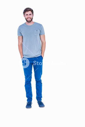 Happy handsome man looking at camera with hands in pocket