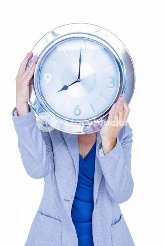 Businesswoman hiding her head with clock