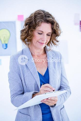 Creative businesswoman taking note on clipboard