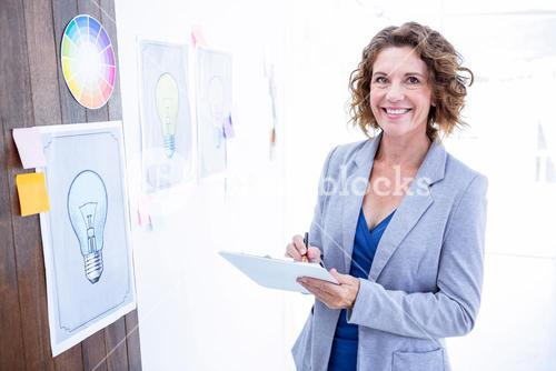 Creative businesswoman looking at camera and taking notes