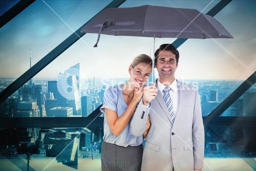 Composite image of business people holding a black umbrella