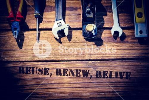Reuse, renew, relive against desk with tools