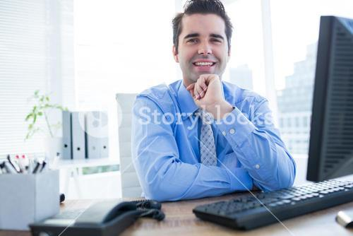Cheerful businessman using computer in office