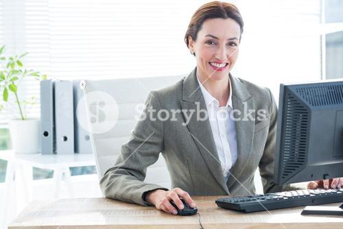 Businesswoman using computer and smiling at camera