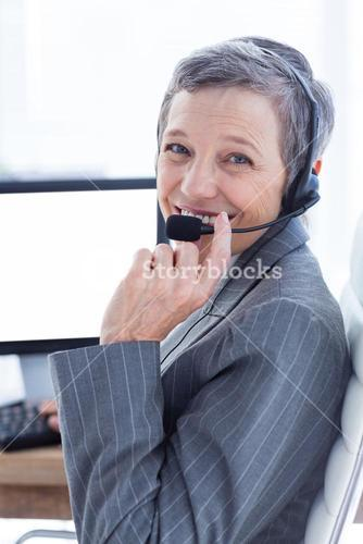 Smiling businesswoman phoning and using computer