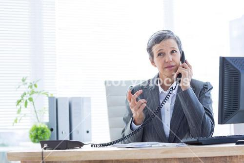 Serious businesswoman phoning and using computer