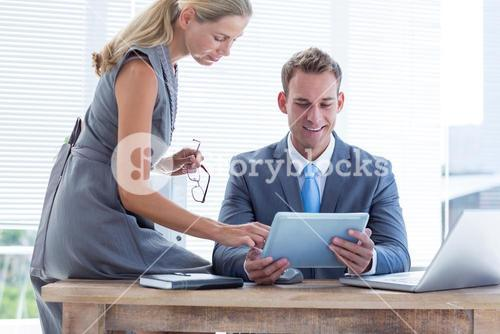 Happy colleagues working together on tablet