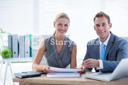 Happy colleagues working together on laptop and folder