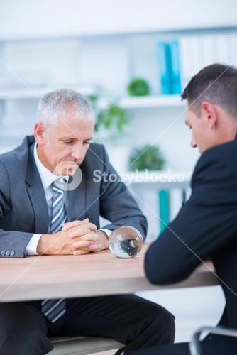 Two businessmen watching crystal ball