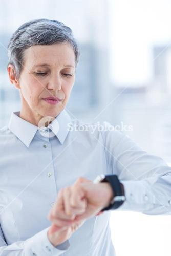 A businesswoman using her smartwatch