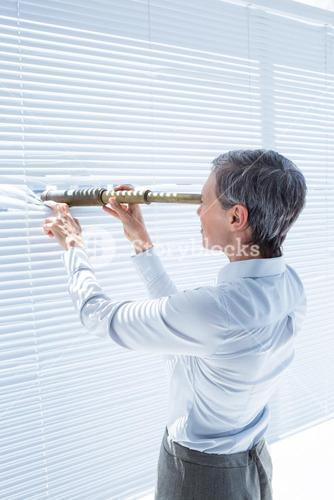 Businesswoman looking through field-glass in the office