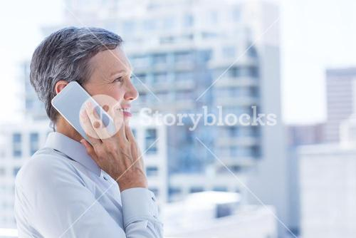 Businesswoman looking through window while on the phone
