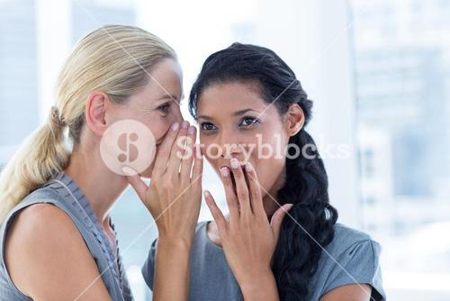 Businesswoman whispering gossip to her colleague