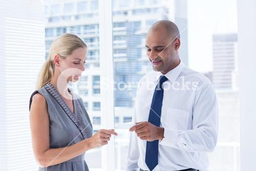 Businessman giving small paper sheet to his colleague