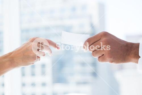 Hands giving small paper sheet to another one