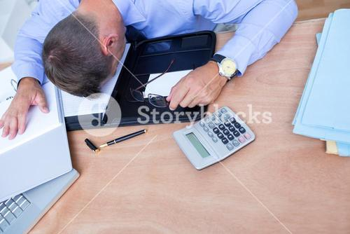 Exhausted businessman sleeping on the desk