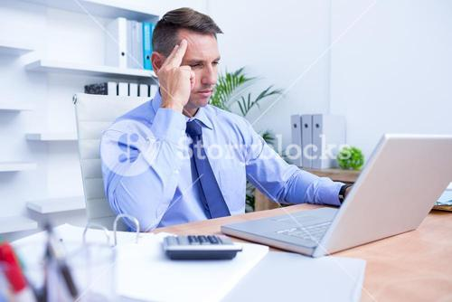 Businessman with severe headache sitting at office desk