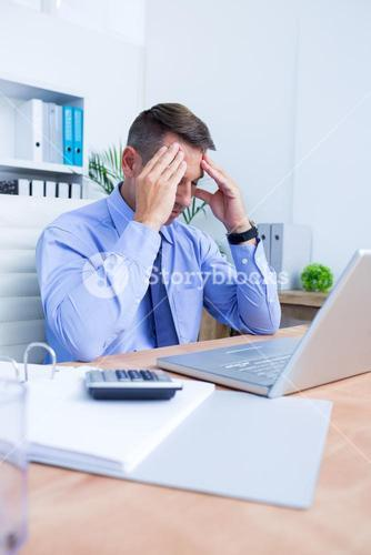 Businessman with severe headache holding his head