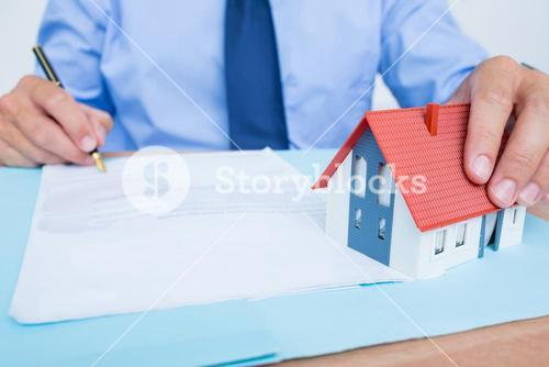 Businessman reading and writing a contrat before signing it