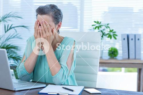 Anxious businesswoman with head in hands