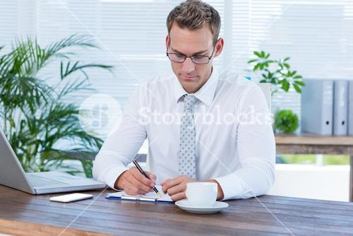 Concentrated businessman writing on a notebook