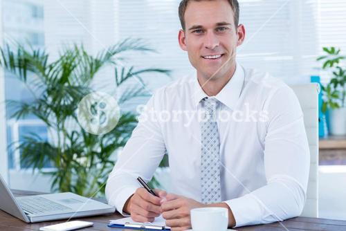 Smiling businessman writing on notebook