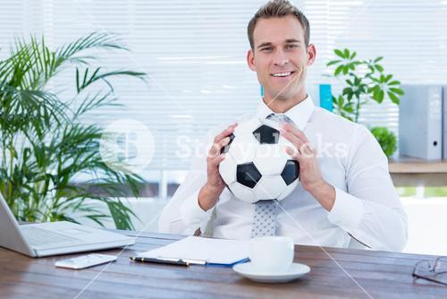Smiling businessman holding a football