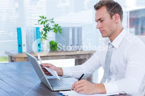 Attentive businessman writing on notebook