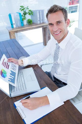 Smiling businessman working with flow charts