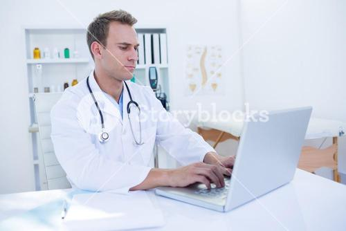 Focused doctor working with laptop