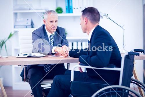 Businessman in wheelchair speaking with colleague