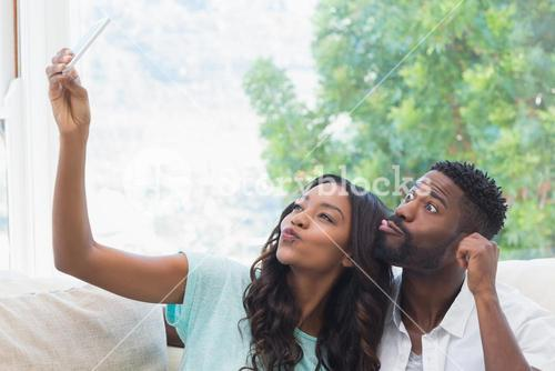 Happy couple on the couch taking selfie