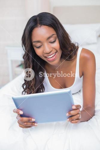 Relaxed woman using tablet pc on bed