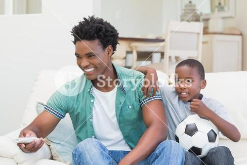 Father and son watching tv together on the couch