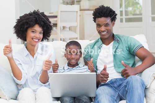 Happy family on the couch with laptop