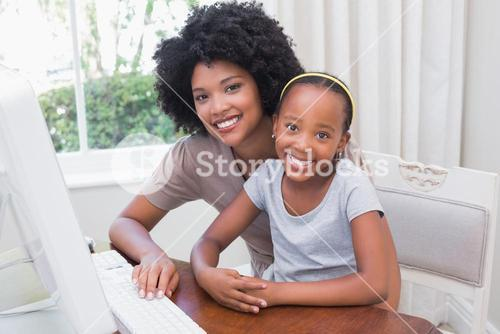 Happy mother and daughter using the computer
