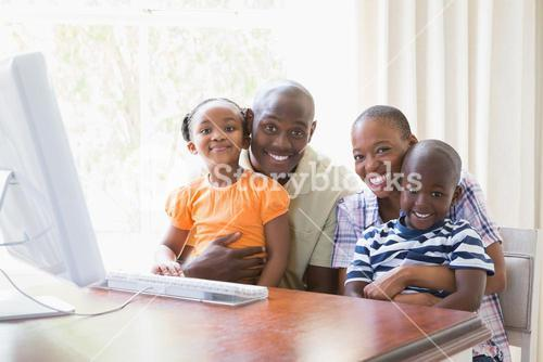 Portrait happy smiling family using computer