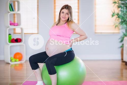 Pregnant woman looking at camera sitting on exercise ball