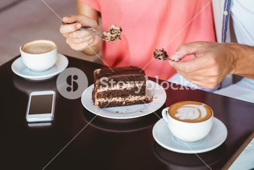 Cute couple on a date sharing a piece of chocolate cake