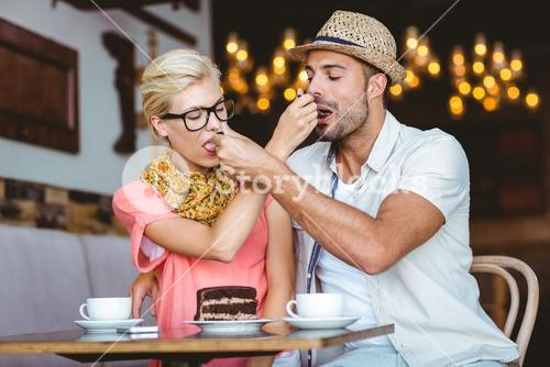 Cute couple on a date giving each other food