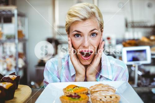Puzzled pretty woman looking at a fruit pie