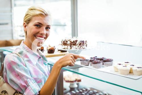 Pretty woman pointing at cup cakes