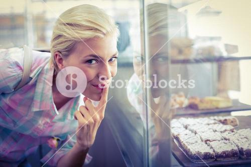 Hesitating pretty woman looking at cup cakes