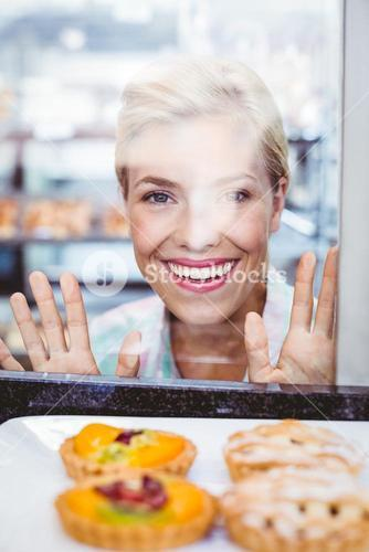 Smiling pretty woman looking at a fruit pie through the glass