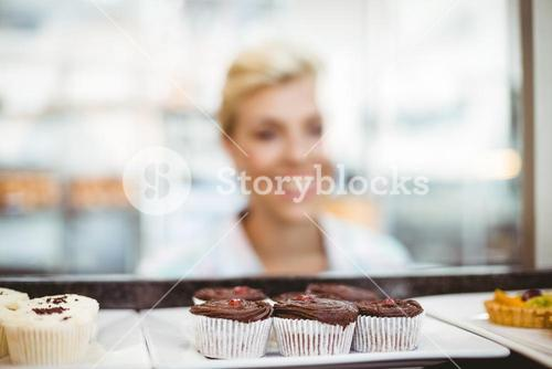 Pretty woman looking at cup cakes