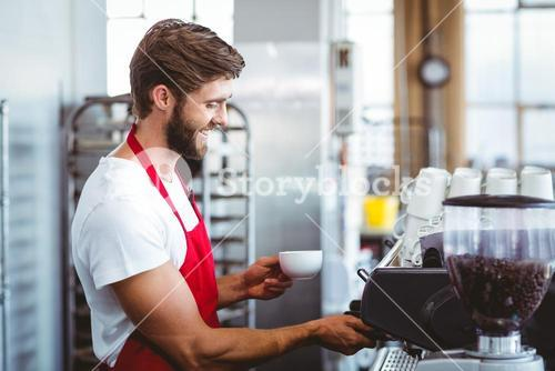 Handsome barista using the coffee machine