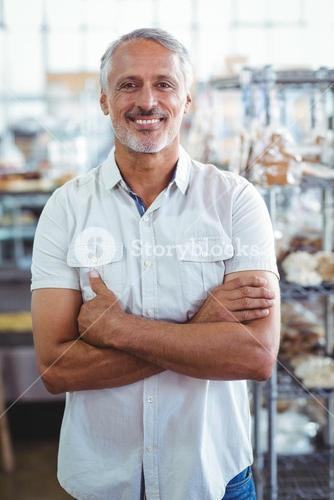 Smiling bakery owner standing with arms crossed