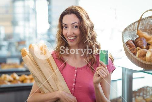Pretty brunette holding credit card and baguettes